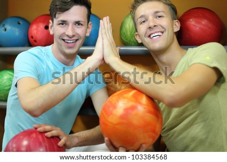 Two happy men sit near shelves with balls, touch hands and look at camera in bowling club; shallow depth of field - stock photo