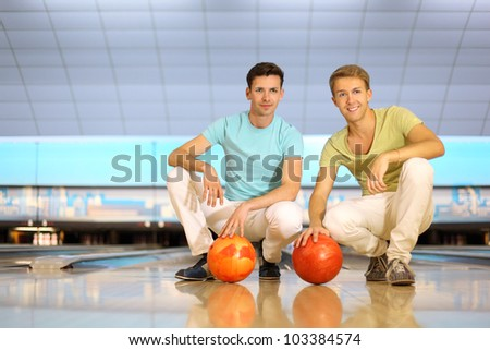 Two happy men sit on floor with orange balls in bowling club; shallow depth of field; full body - stock photo