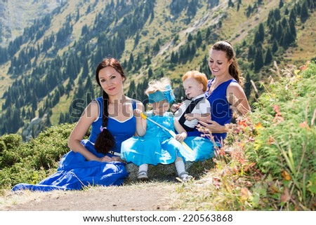 Two happy moms and children girl and boy hugging on nature The concept of childhood and family.  - stock photo