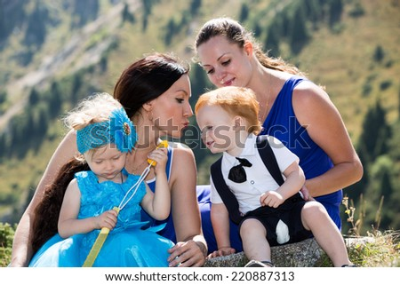 Two happy moms and children girl and boy hugging on nature The concept of childhood and family.
