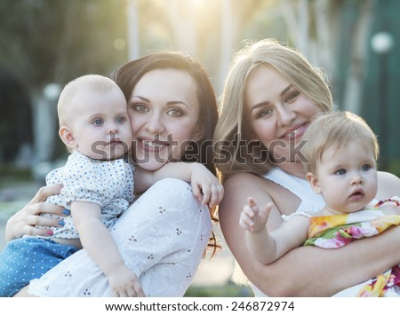 Two happy mothers and their babies enjoy the summer sunset - stock photo
