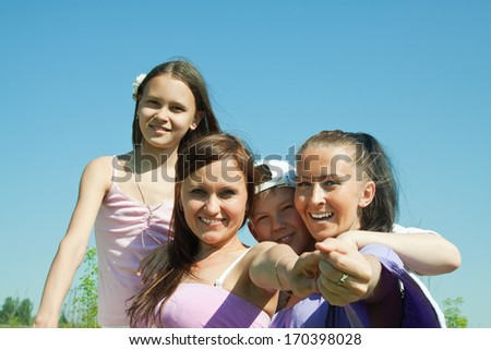 Two happy mothers with teens against blue sky - stock photo