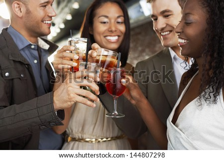 Two happy multiethnic couples toasting drinks at the bar - stock photo