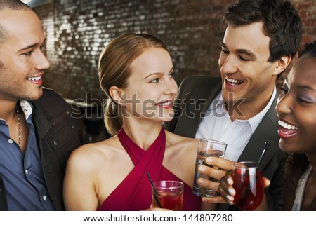 Two happy multiethnic couples with drinks at the bar - stock photo