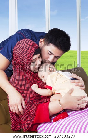 Two happy muslim parents kiss their baby while sleeping on the mother's chest, shot at home