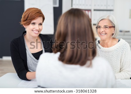 Two Happy Office Women Listening to their Manager at her Table Talking to Them. - stock photo