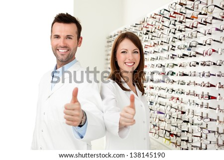 Two happy opticians, optometrists showing thumbs up in optical shop - stock photo