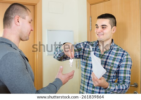 Two happy ordinary men standing at doorway with keys and contract  - stock photo