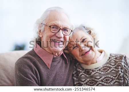 Two happy pensioners looking at camera with smiles - stock photo