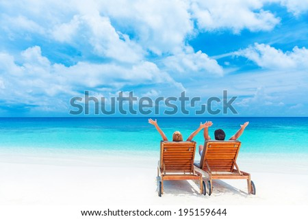 Two happy people having fun on the beach, sitting on comfortable sunbed with raised up hands for joy, rear view, summer holidays concept     - stock photo