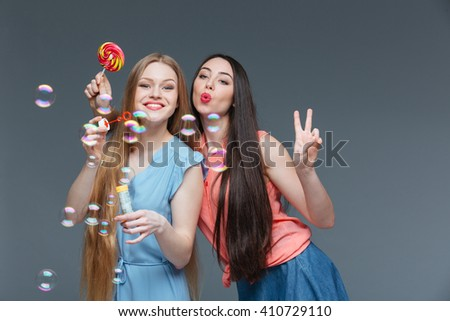 Two happy playful young women with colorful lollipop blowing bubbles over grey background - stock photo