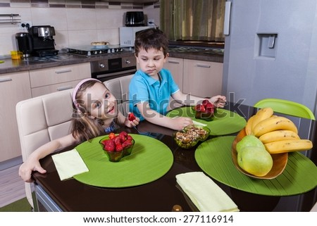 Two happy preschool children who eat healthy strawberry in the kitchen - stock photo