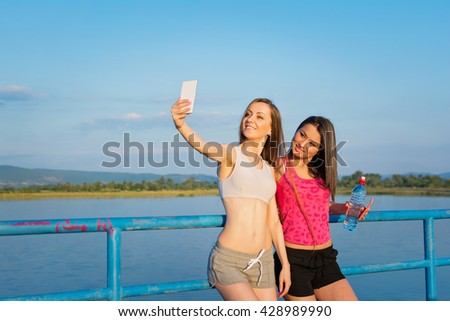 Two happy runner women taking a selfie outdoors on sunny summer day. Two sporty girlfriends photographing themselves on smartphone at the beach. Vibrant colors, mild retouch, natural light - stock photo