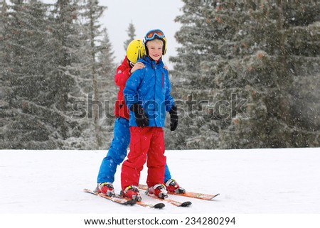 Two happy school boys, twin brothers in colorful snowsuits, having fun skiing in alpine mountains during snowy winter vacation - stock photo