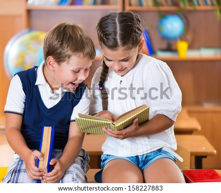 Two happy schoolchildren have fun in classroom at school