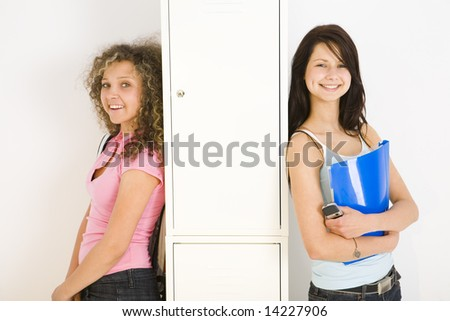 Two happy schoolgirl standing and leaning for shool locker. One of them holding notebook and mobilephone. looking at camera. - stock photo