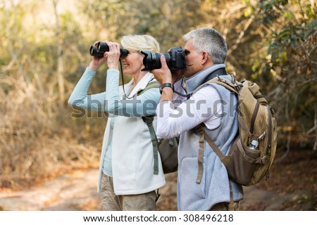 two happy senior hikers at valley of the mountain - stock photo