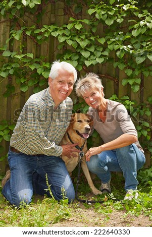 Two happy senior people sitting with a dog in a garden - stock photo