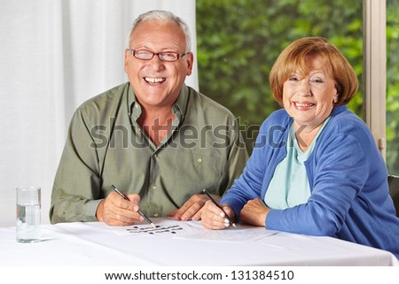Two happy senior people solving riddles in a retirement home - stock photo