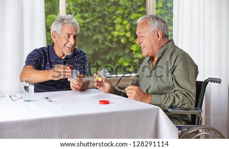 Two happy senior people taking medication in a nursing home - stock photo