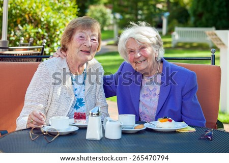 Two Happy Senior Women Relaxing at the Garden Table with Cups of Coffee and Snacks, Looking at the Camera. - stock photo