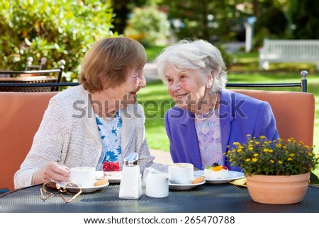 Two Happy Senior Women Sitting and Chatting at the Outdoor Table with Coffee and Snacks - stock photo