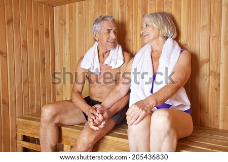 Two happy seniors holding their hands in a sauna in a hotel - stock photo