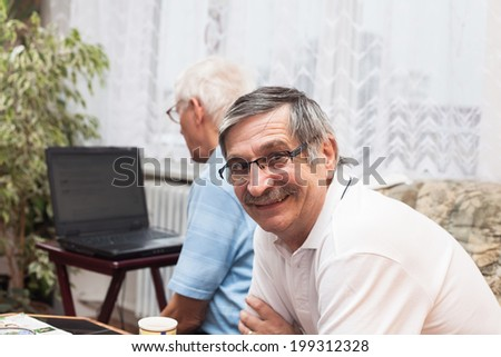 Two happy seniors learning to use a computer.