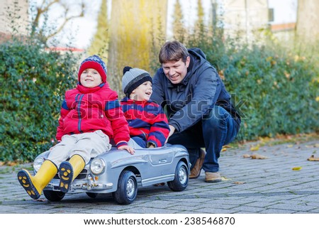 Two happy sibling boys and father playing with big old toy car, outdoors. Family of three having fun together on cold sunny autumn or spring day. - stock photo