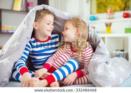 Two happy sibling children hiding under blanket