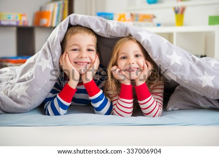 Two happy sibling children lying under blanket