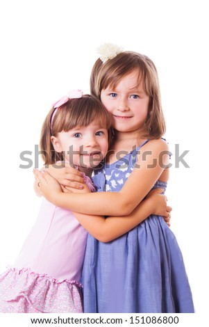 Two happy sisters hugging isolated on white