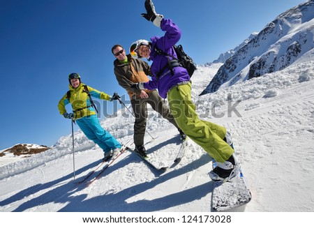 Two happy skiers and snowboarder on the slope at a ski resort in the Alps - stock photo