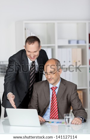 Two happy smiling cheerful businesspeople working with laptop at office