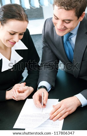 Two happy smiling cheerful young businesspeople working with documents at office