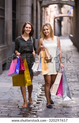 Two happy smiling girls walking by street with shopping bags