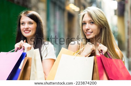 Two happy smiling girls walking by street with shopping bags in hands  - stock photo