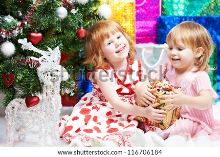 Two happy smiling little girls with gifts near decorated new year tree before Christmas - stock photo