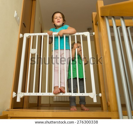 Two happy smiling little sisters near stair gate at home - stock photo