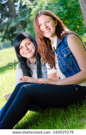 Two happy smiling & looking at camera young teenage girls students sitting in park with tablet pc on summer outdoors background - stock photo
