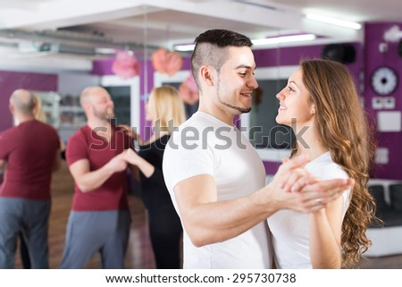 Two happy smiling loving couples having dancing class in club - stock photo