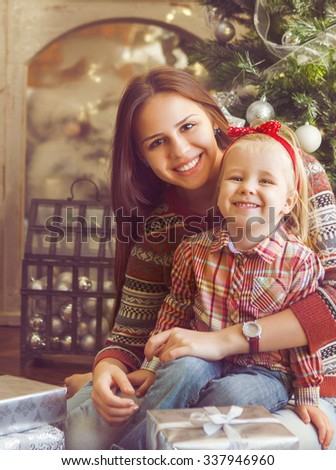 Two happy smiling sisters sitting by the Christmas tree - stock photo