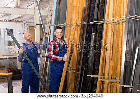 Two happy smiling workmen choosing PVC window profile at stand - stock photo