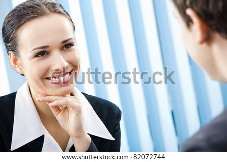 Two happy smiling young businesspeople, or business woman and client, working at office - stock photo