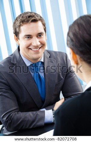 Two happy smiling young businesspeople, or businessman and client, working at office - stock photo