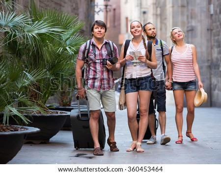Two happy smiling young couples with travel bags walking through the city. Selective focus - stock photo