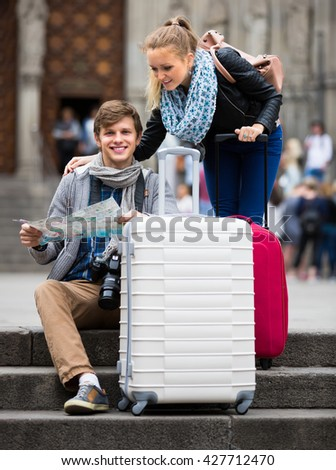 Two happy smiling young travelers with city map and baggage looking for hotel - stock photo