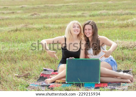 Two happy student girls holding board for writing - stock photo