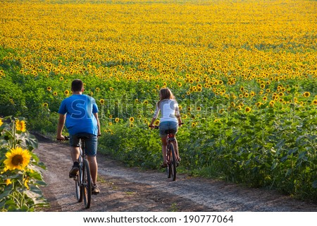 Two happy teen cyclist in sunflower field riding bicycle - stock photo