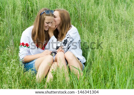 Two happy teen girl friends whispering secret on bright summer day outdoors - stock photo